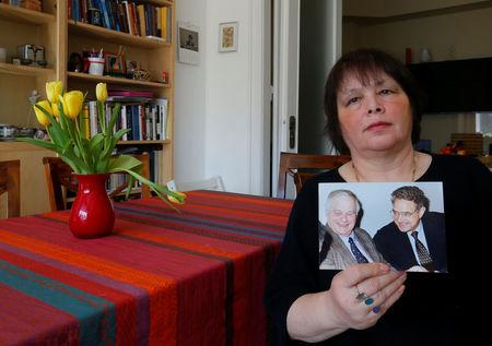 Maria Vasarhelyi, a Hungarian sociologist and opposition activist, holds a picture of billionaire philanthropist George Soros with her late father Miklos Vasarhelyi, who led the Soros Foundation in Hungary in the 1980s and 1990s, in Budapest, Hungary, March 3, 2017.  REUTERS/Laszlo Balogh