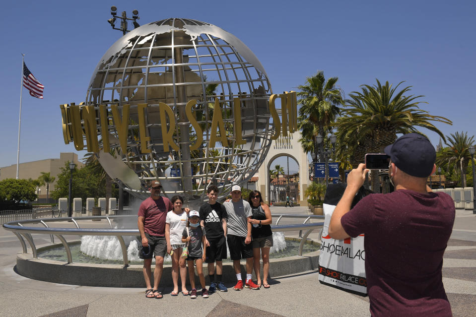 A family has their picture taken at Universal CityWalk, Thursday, June 11, 2020, near Universal City, Calif. The tourist attraction, which had been closed due to the coronavirus outbreak recently re-opened. The Universal Studios tour is still closed. (AP Photo/Mark J. Terrill)