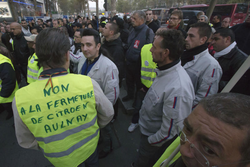 "CORRECTS TO THURSDAY  Workers of Peugeot Citroen gathering outside the company headquarters to protest against job cuts in Paris, Thursday, Oct. 25, 2012. France is offering a Euro 7 billion ($9.1 billion ) lifeline to PSA Peugeot Citroen, the carmaker confirmed Wednesday alongside another drop in sales. Traffic safety jacket reads: ""no to the closure of Citroen Aulnay plant"". (AP Photo/Michel Euler)"
