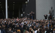 Newcastle United supporters celebrate outside St. James' Park in Newcastle Upon Tyne, England Thursday Oct. 7, 2021. English Premier League club Newcastle has been sold to Saudi Arabia's sovereign wealth fund after a protracted takeover and legal fight involving concerns about piracy and rights abuses in the kingdom. (AP Photo/Scott Heppell)