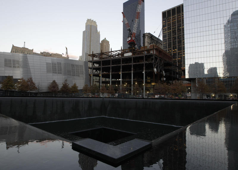 Surrounding buildings are seen in one of the two reflecting pools at the World Trade Center Memorial where water running again after it had been shut down due to flooding in the wake of Superstorm Sandy, Monday, Nov. 5, 2012, in New York.  Joe Daniels, president of the September 11 Memorial and Museum, said water that rushed into the site has been pumped out. and the memorial will re-open to the public Tuesday.  (AP Photo/Kathy Willens)