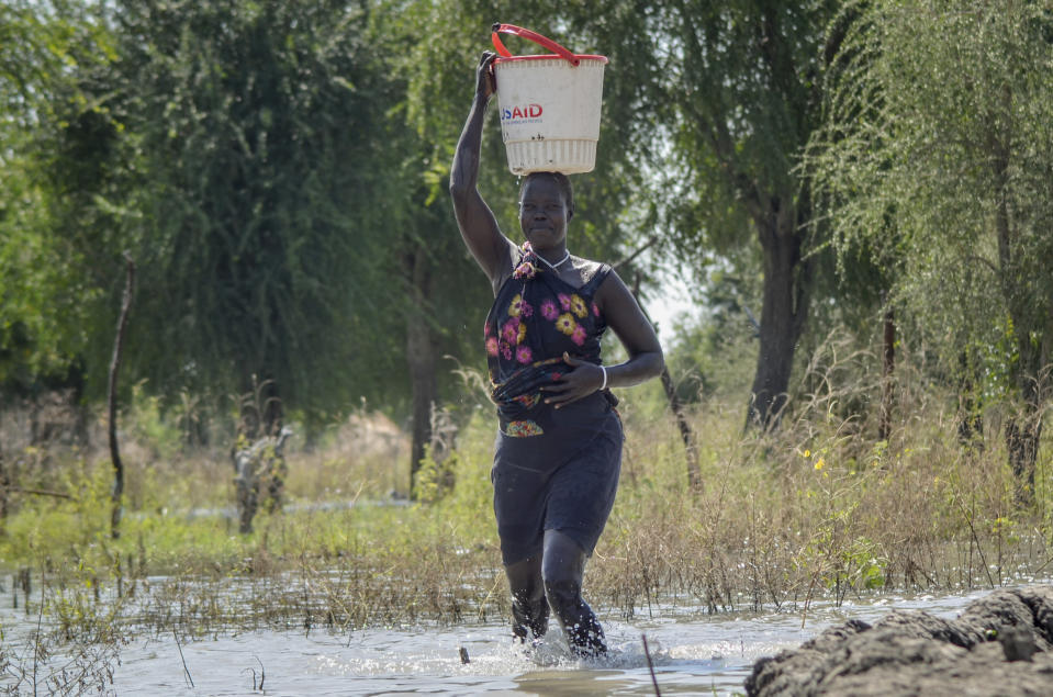 Mother of five Nyaduoth Kon, carries food in a bucket on her head as she wades through floodwaters in the village of Wang Chot, Old Fangak county, Jonglei state, South Sudan Thursday, Nov. 26, 2020. Some 1 million people in the country have been displaced or isolated for months by the worst flooding in memory, with the intense rainy season a sign of climate change. (AP Photo/Maura Ajak)