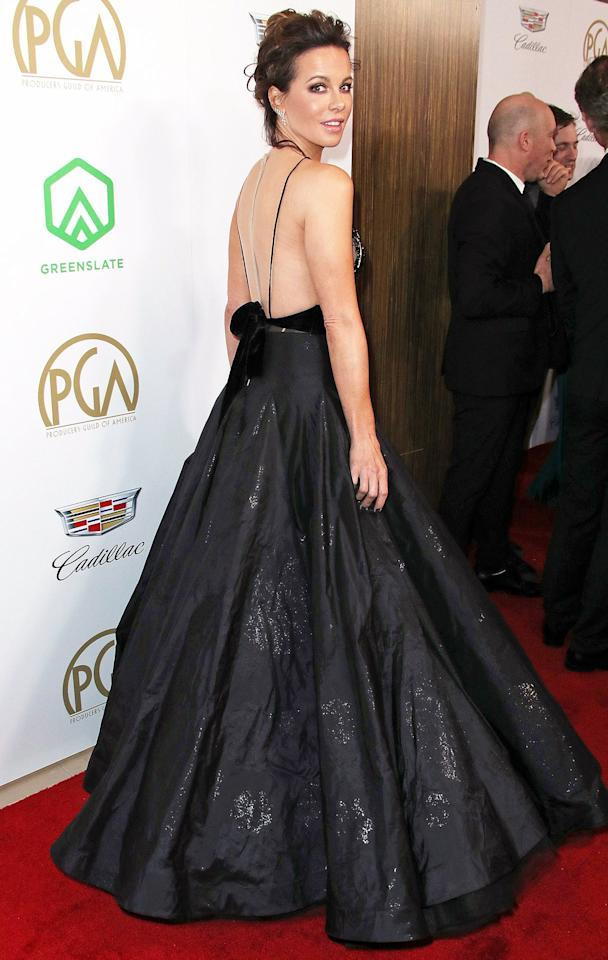 in a plunging black gown with feather and sheen accents at the 30th Annual Producers Guild Awards.
