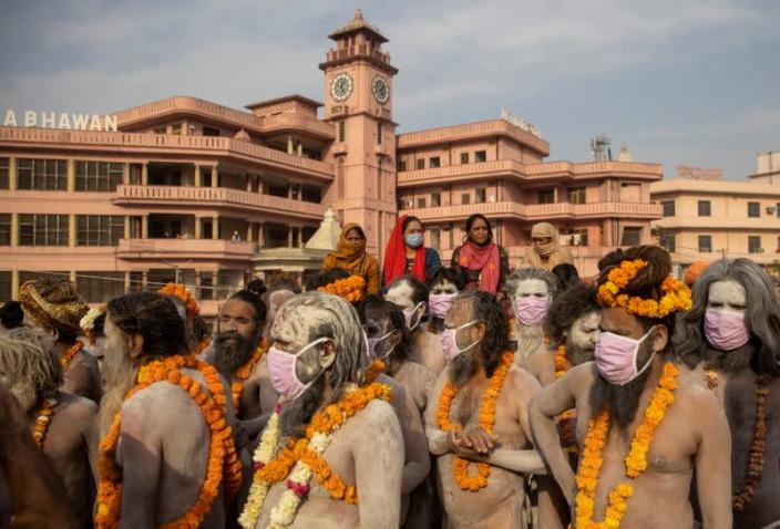 """Naga Sadhus, or Hindu holy men wearing face masks wait before the procession for taking a dip in the Ganges river during Shahi Snan at """"Kumbh Mela"""", or the Pitcher Festival, amidst the spread of the coronavirus disease (COVID-19), in Haridwar"""