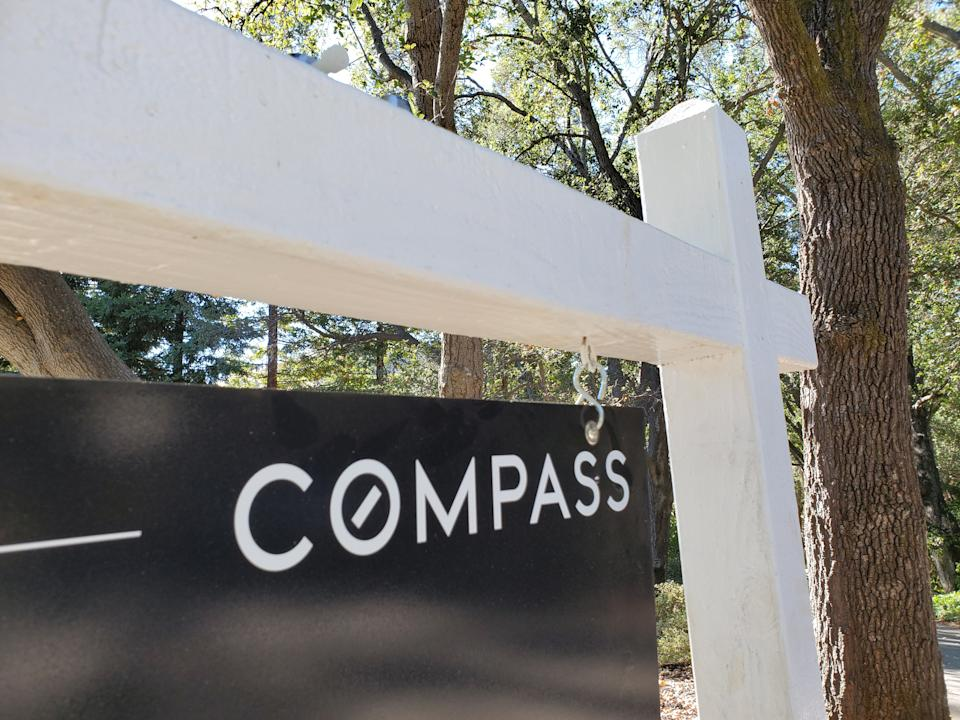 Close-up of a Compass Real Estate hanging sign panel in a wooded area, Lafayette, California, October 21, 2020. (Photo by Smith Collection/Gado/Getty Images)
