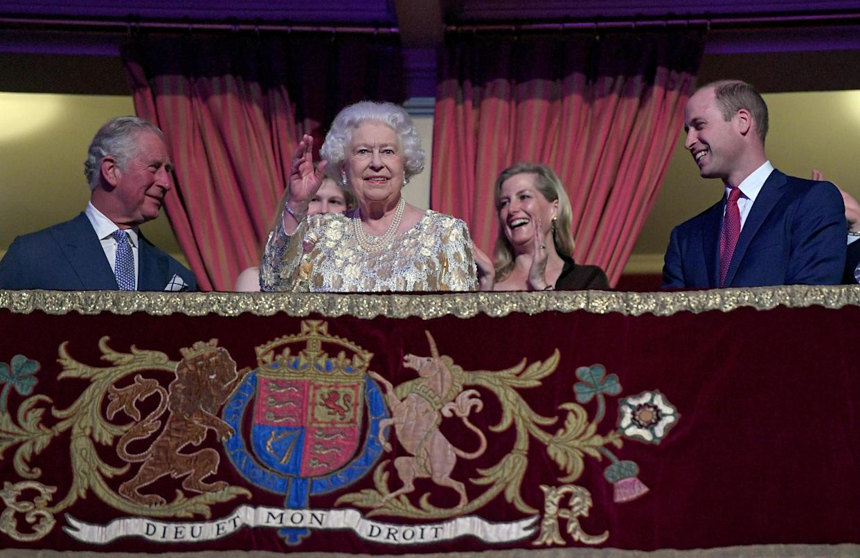 TOPSHOT - Britain's Queen Elizabeth II (centre L) waves to guests as her son Britain's Prince Charles, Prince of Wales (L) and grandson Britain's Prince William, Duke of Cambridge (R) react as she takes her seat ni the Royal box during The Queen's Birthday Party concert on the occassion of Her Majesty's 92nd birthday at the Royal Albert Hall in London on April 21, 2018. (Photo by Andrew Parsons / POOL / AFP) (Photo by ANDREW PARSONS/POOL/AFP via Getty Images)