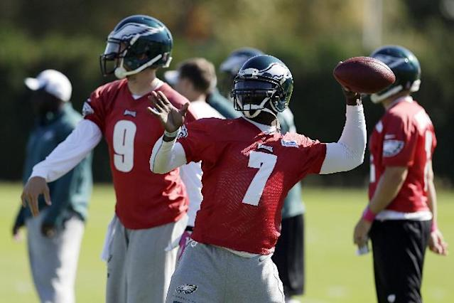 Philadelphia Eagles quarterback Michael Vick, right, and Nick Foles throw passes during practice at the NFL football team's training facility, Tuesday, Oct. 15, 2013, in Philadelphia. (AP Photo/Matt Rourke)