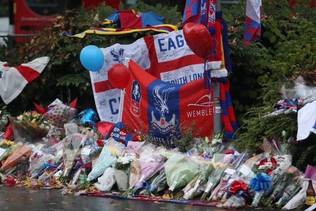 Floral tributes and Crystal Palace football colours left near the scene where a tram crashed, killing seven people, in Croydon, south London (Steve Parsons/PA)