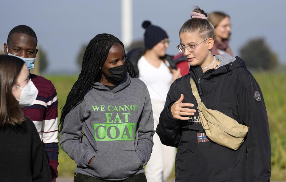 Climate activists Vanessa Nakate from Uganda and Leonie Bremer of the German Fridays for Future movement, right, visit the Garzweiler open-cast coal mine in Luetzerath, western Germany, Saturday, Oct. 9, 2021. Garzweiler, operated by utility giant RWE, has become a focus of protests by people who want Germany to stop extracting and burning coal as soon as possible. The village of Luetzerath, now almost entirely abandoned as the mine draws ever closer, will be the latest village to disappear as coal mining at the Garzweiler mine expands. (AP Photo/Martin Meissner)