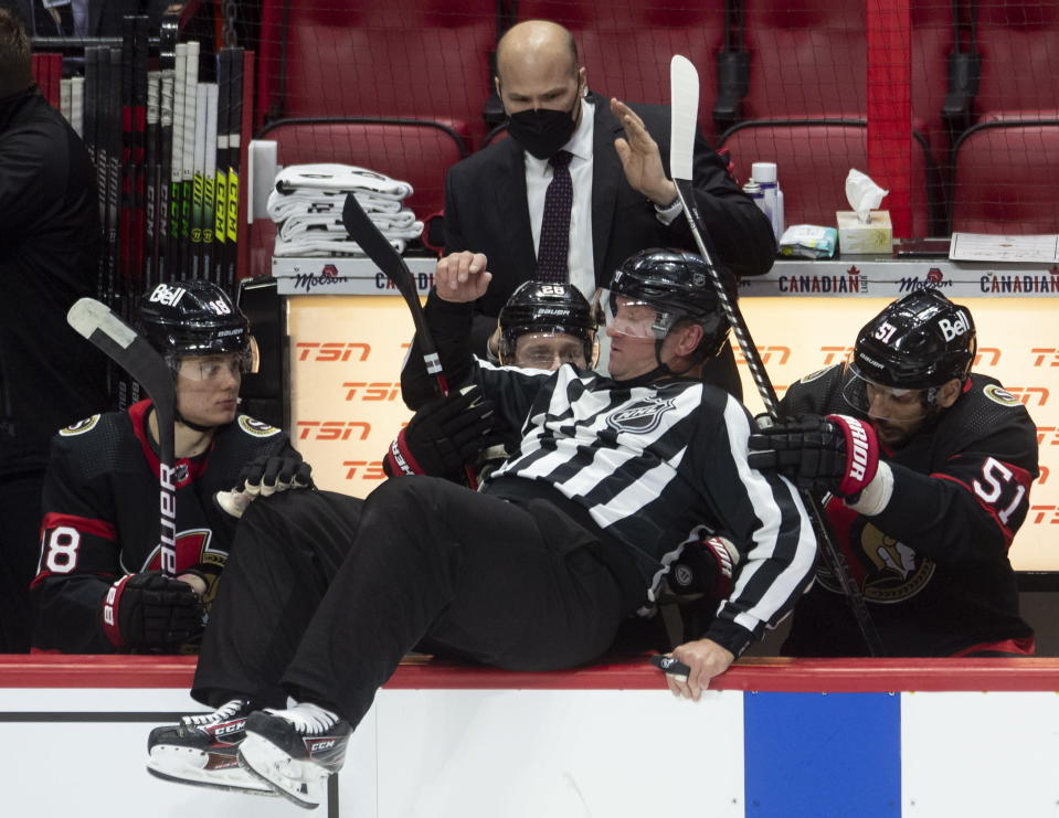 Ottawa Senators players help linesman Derek Nansen as he falls into the bench while avoiding a shot along the boards during the second period of an NHL hockey game between the Senators and the Edmonton Oilers on Wednesday, April 7, 2021, in Ottawa, Ontario. (Adrian Wyld/The Canadian Press via AP)