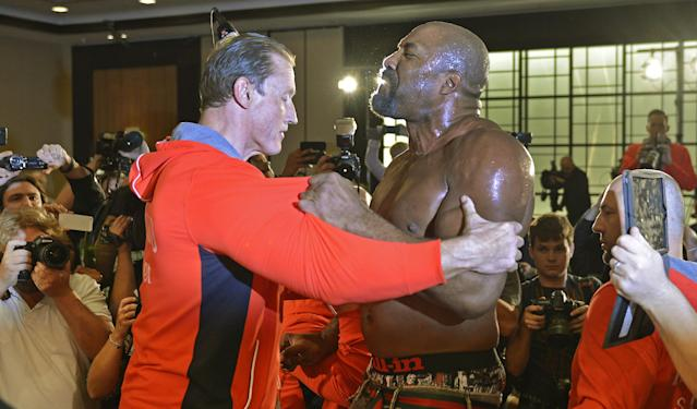 Former heavyweight world champion Shannon Briggs of the US, is pushed back by security after showing up at a press conference of boxer Wladimir Klitschko of Ukraine during a press conference ahead of Klithscko's IBF, IBO, WBO and WBA heavyweight title bout against challenger Alex Leapai from Australia-Samoa in Duesseldorf, Germany, April 22, 2014. Briggs demanded a title fight against Klitschko in the US. (AP Photo/Martin Meissner)