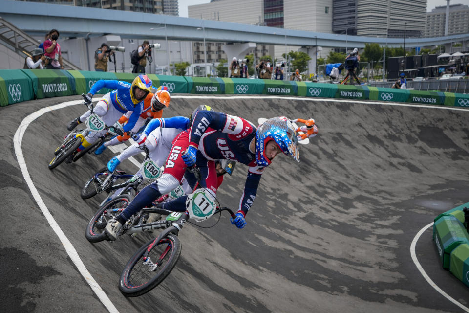 Connor Fields of the United States, center, who later crashed, is followed by Romain Mahieu of France, center-left, and Vincent Pelluard of Colombia, left, as they compete in the men's BMX Racing semifinals at the 2020 Summer Olympics, Friday, July 30, 2021, in Tokyo, Japan. (AP Photo/Ben Curtis)