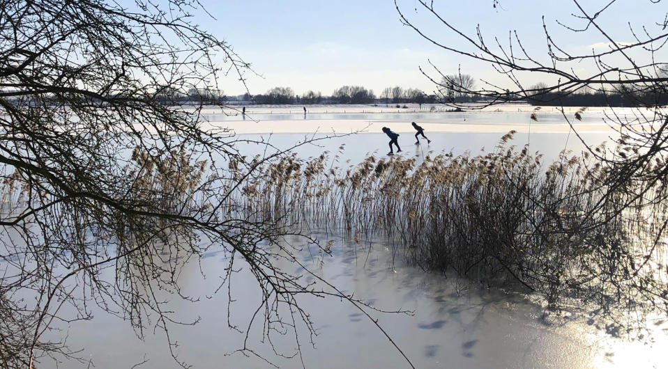 People skate on Nederrijn river near Doorwerth, Netherlands, Thursday, Feb. 11, 2021. The deep freeze gripping parts of Europe served up fun and frustration with heavy snow cutting power to some 37,000 homes in central Slovakia. (AP Photo/Aleksandar Furtula)