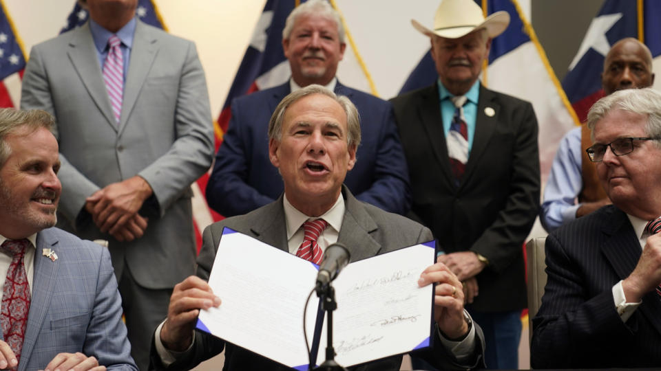 Texas Gov. Greg Abbott shows off his signature after signing Senate Bill 1, also known as the election integrity bill, into law in Tyler, Texas, on Tuesday. He is flanked by State Sen. Bryan Hughes, R-Mineola, front center left, and Lieutenant Gov. Dan Patrick, front right.