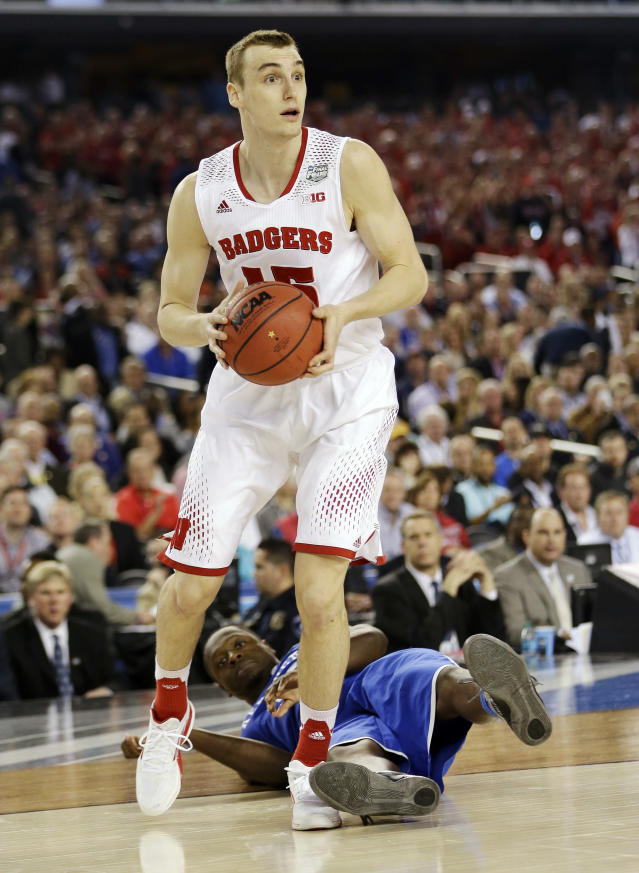 Wisconsin forward Sam Dekker (15) controls the ball as Kentucky forward Julius Randle hits the floor during the second half of the NCAA Final Four tournament college basketball semifinal game Saturday, April 5, 2014, in Arlington, Texas. (AP Photo/David J. Phillip)