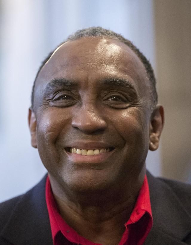 Johnny Rodgers, the 1972 Heisman Trophy winner, smiles at the Nebraska state board of pardons hearing in Lincoln, Neb., Thursday, Nov. 14, 2013, after he was granted a pardon for his felony conviction for robbing a gas station in 1970. (AP Photo/Nati Harnik)