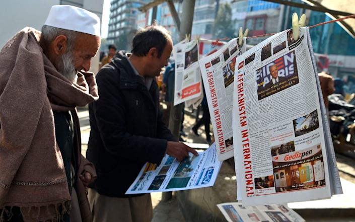 Two men looking at newspapers clipped to wire at a newsstand - Wakil Kohsar/AFP