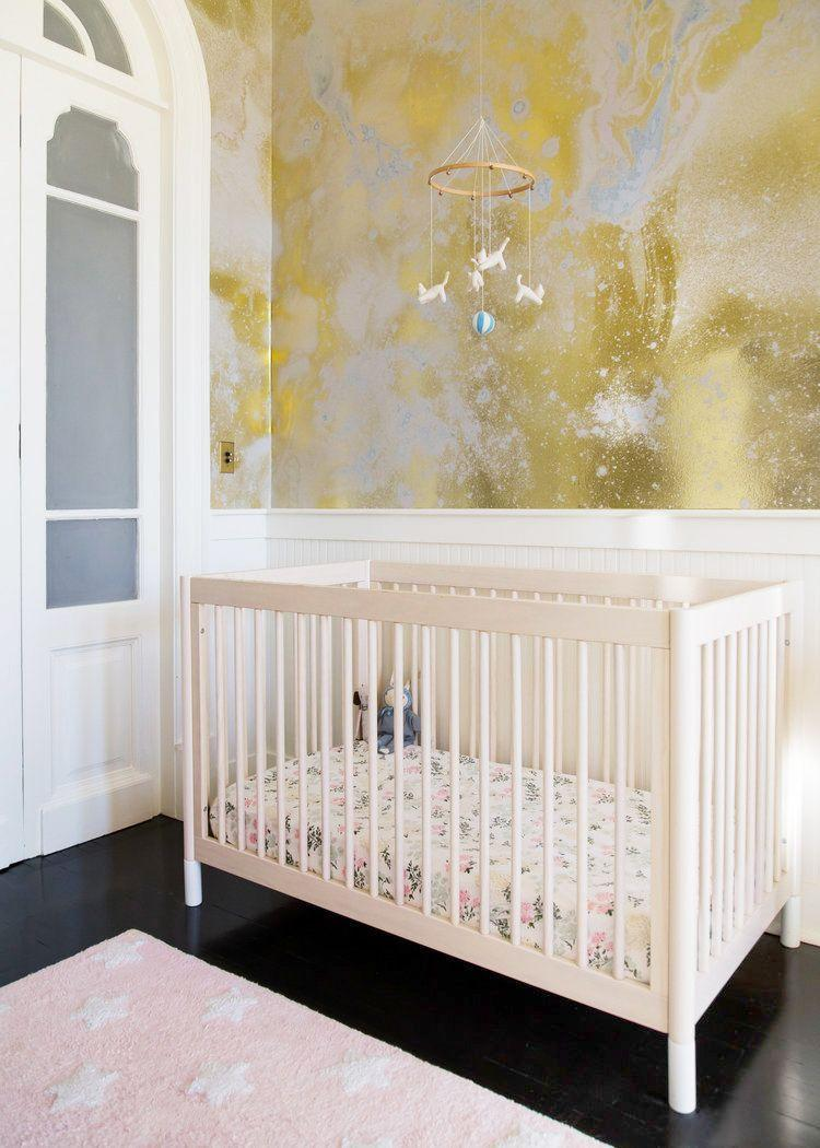 """<p>Use a contemporary wallpaper with a metallic sheen for a dreamy. ethereal feel. In this nursery designed by <a href=""""https://thewhitearrow.com/"""" rel=""""nofollow noopener"""" target=""""_blank"""" data-ylk=""""slk:White Arrow,"""" class=""""link rapid-noclick-resp"""">White Arrow,</a> the abstract Calico Wallpaper will still add some beauty and style no matter how the space is used in the future. </p>"""