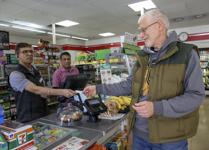 George Brichacek, of Carol Stream, buys his lottery tickets for the Mega Millions lottery drawing in Carol Stream, Ill. on Monday, Oct. 22, 2018. (Bev Horne/Daily Herald via AP)