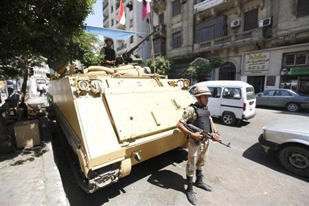 A soldier stands next to an armoured personnel carrier (APC) near the al-Fath mosque on Ramses Square in Cairo