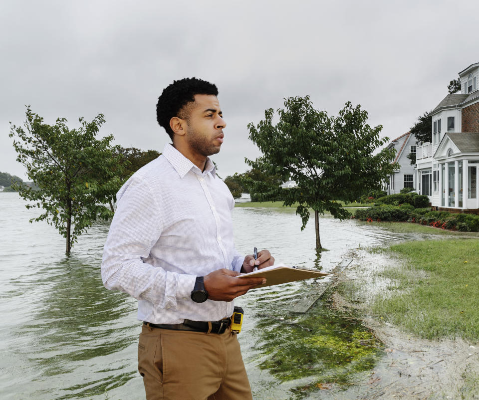 Black insurance adjuster examining flooding damage to house