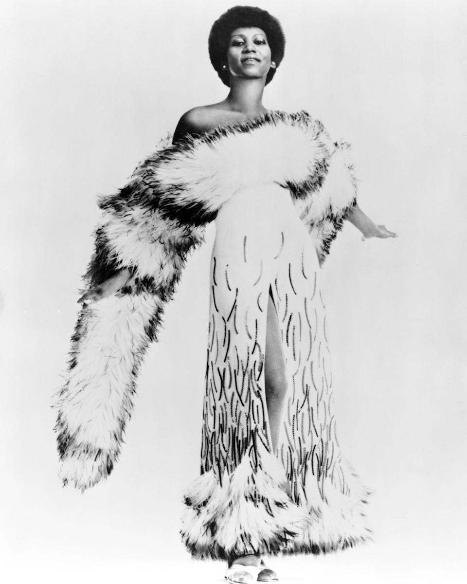 """<p>The """"Queen of Soul"""" wears a luxurious gown with intricate embroideries and a fur trim hem along with a large fur stole around her shoulder. Her 'fro really sets off the look. (Photo by Michael Ochs Archives/Getty Images) </p>"""