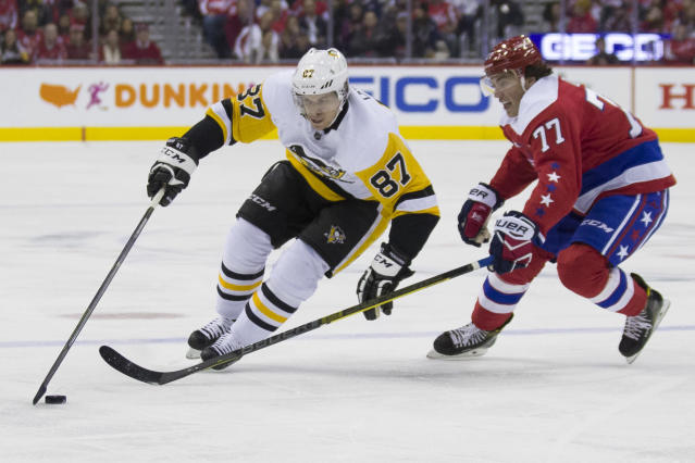 Pittsburgh Penguins center Sidney Crosby (87) gets away from Washington Capitals right wing T.J. Oshie (77) in the first period of an NHL hockey game, Wednesday, Dec. 19, 2018, in Washington. (AP Photo/Alex Brandon)