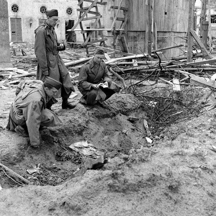 """Unpublished: LIFE correspondent Percy Knauth (left) sifts through debris in the shallow trench in the garden of the Reich Chancellery where, Knauth was told, the bodies of Hitler and Eva Braun were burned after their suicides. (William Vandivert—Time & Life Pictures/Getty Images) <br> <br> <a href=""""http://life.time.com/history/inside-hitlers-bunker-rare-and-unpublished-photos/#1"""" rel=""""nofollow noopener"""" target=""""_blank"""" data-ylk=""""slk:Click here"""" class=""""link rapid-noclick-resp"""">Click here</a> to see the complete collection of pictures and read the full story at LIFE.com"""