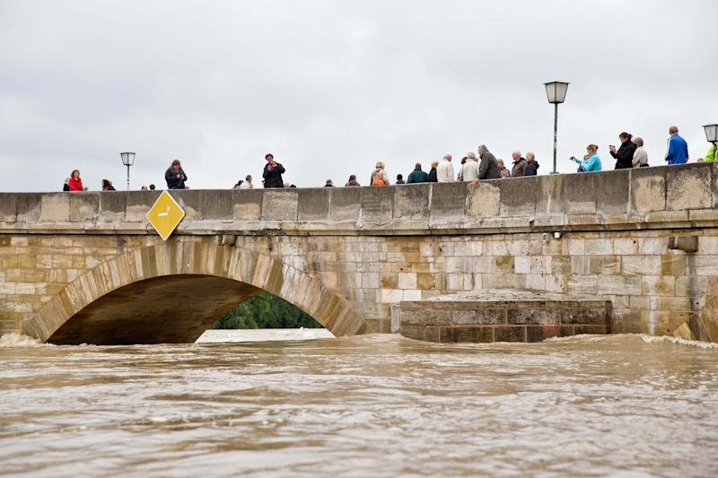 Persons cross the Stone Bridge over Danube river in Regensburg,Germany, Tuesday June 4, 2013. Heavy rains are causing serious flooding in Germany, Austria and Czech Republic. (AP Photo/dpa,Daniel Karmann)