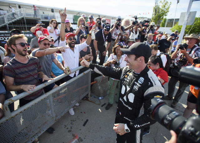 Simon Pagenaud, right, of France, celebrates with fans after winning the Honda Indy auto race in Toronto, Sunday, July 14, 2019. (Andrew Lahodynskyj/The Canadian Press via AP)