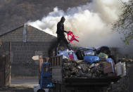 A man loads possessions on his truck after setting his home on fire, in an area once occupied by Armenian forces but is soon to be turned over to Azerbaijan, in Karvachar, the separatist region of Nagorno-Karabakh, on Friday, Nov. 13, 2020. Under an agreement ending weeks of intense fighting over the Nagorno-Karabakh region, some Armenian-held territories adjacent to the region are passing to Azerbaijan. (AP Photo/Dmitry Lovetsky)