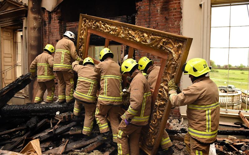 A Picture frame is removed from Clandon Park following the fire - National Trust