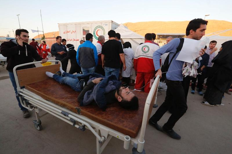 An Iranian quake victim is transported on a hospital bed to receive treatment at a field hospital in the town of Sar-e Pol-e Zahab on November 14, 2017 (AFP Photo/ATTA KENARE)