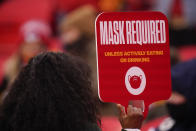 FILE - In this Jan. 3, 2021, file photo, an Arrowhead Stadium usher holds a mask required sign during the first half of an NFL football game in Kansas City. At least for now, U.S. health authorities say after being vaccinated, people should follow the same rules as everybody else about wearing a mask, keeping a 6-foot distance and avoiding crowds even after they've gotten their second vaccine dose. (AP Photo/Jeff Roberson, File)