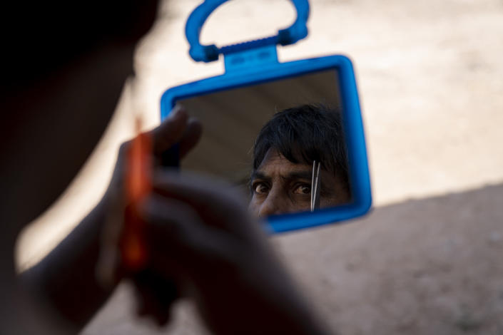 A migrant worker trims his eyebrows at his living quarters on a palm oil plantation run by government-owned Felda in Malaysia in early 2020. Jum, a former worker who escaped from this same plantation, described to The Associated Press how the company confiscated and later lost his Indonesian passport, leaving him vulnerable to arrest and forcing him to hide in the jungle. (AP Photo/Ore Huiying)