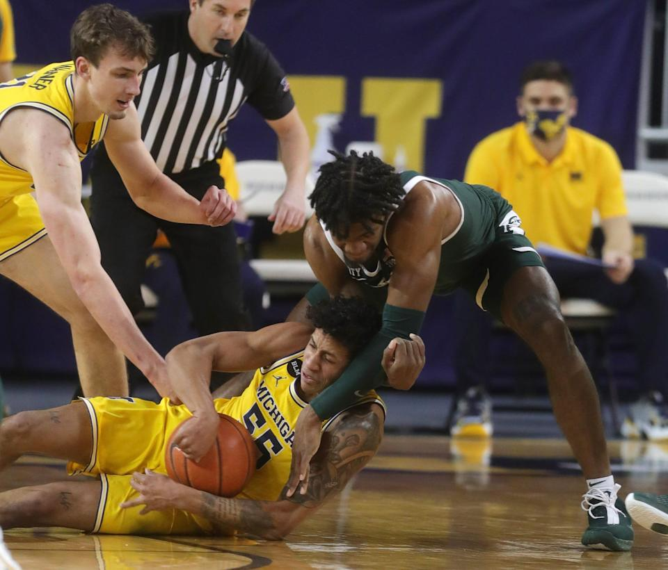 Michigan Wolverines guard Eli Brooks goes for the loose ball against Michigan State Spartans forward Aaron Henry on Thursday, March 4, 2021 at Crisler Center in Ann Arbor.