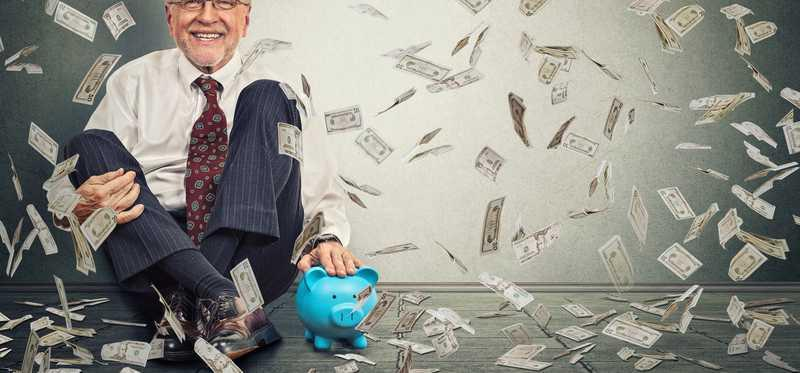 An older man sits by his piggy bank as money flies through the air.