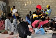 Ethiopian migrants rest before they were flown back to Ethiopia, at an IOM shelter in Aden