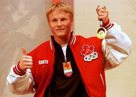FILE PHOTO: Canadian snowboarder Ross Rebagliati holds his Olympic snowboarding giant slalom gold medal February 13 during a news conference. The international sports arbitration panel announced his Olympic disqualification had been reversed and he could keep his gold medal.   /File Photo