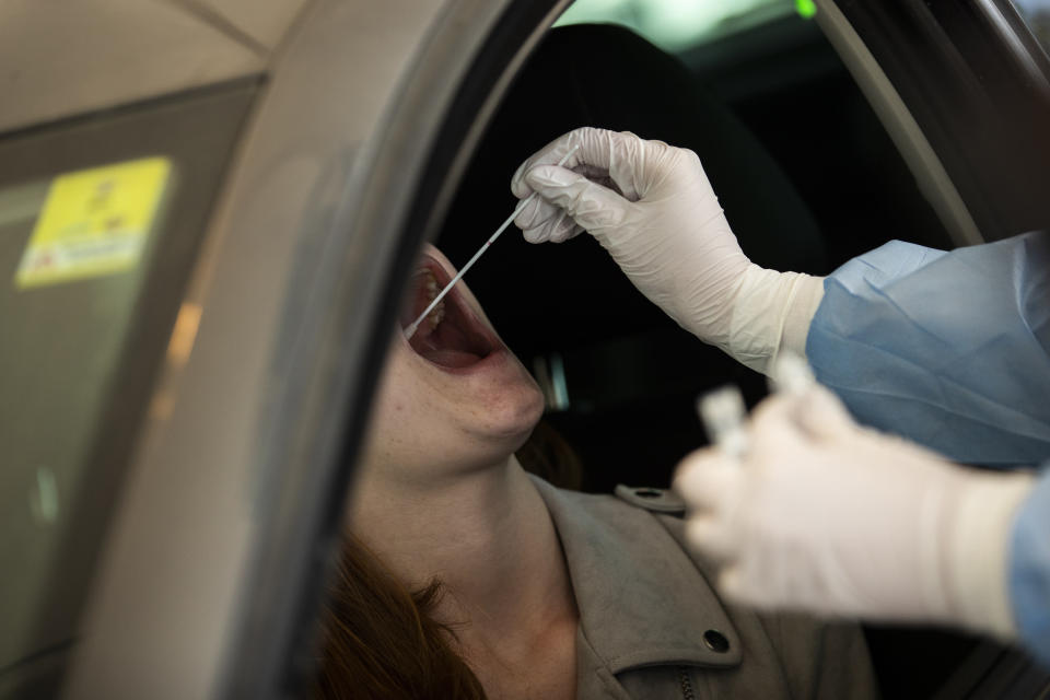 A member of medical personnel, wearing a full protective equipment, takes a mouth swab sample from a woman to be tested for coronavirus COVID-19 in a drive-in station in Luxembourg, Wednesday, May 27, 2020. Luxembourg has launch on Wednesday a nation wide coronavirus testing campaign among its population and commuters. (AP Photo/Francisco Seco)