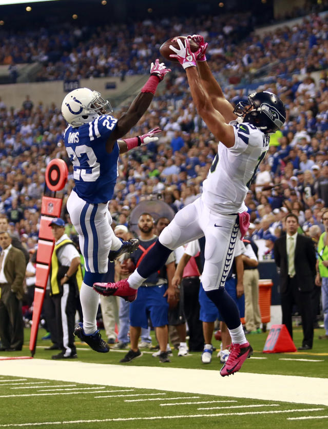 Seattle Seahawks wide receiver Jermaine Kearse, right, scores a touchdown on a catch in front of Indianapolis Colts cornerback Vontae Davis during the first half of an NFL football game in Indianapolis, Sunday, Oct. 6, 2013. (AP Photo/Brent R. Smith)