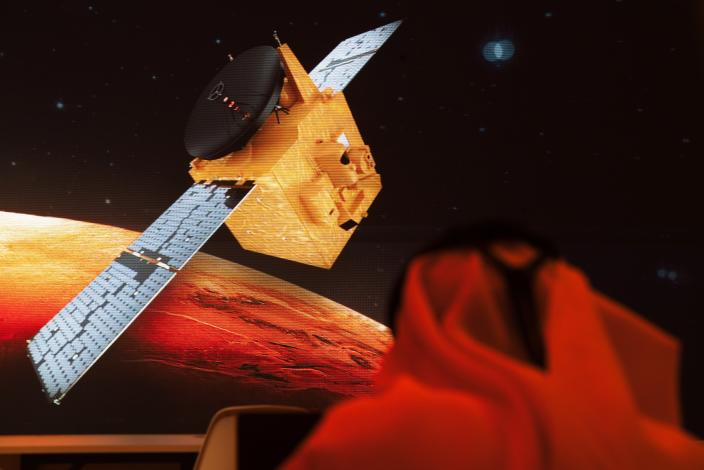 An Emirati television journalist works on a script as a graphic showing the Emirates' Hope space probe to Mars flashes past him on a screen at the Mohammed bin Rashid Space Center in Dubai, United Arab Emirates, Sunday, July 19, 2020. A Japanese H-IIA rocket carrying a United Arab Emirates Mars spacecraft has been placed on the launch pad for Monday's scheduled liftoff for the Arab world's first interplanetary mission, officials said Sunday. (AP Photo/Jon Gambrell)