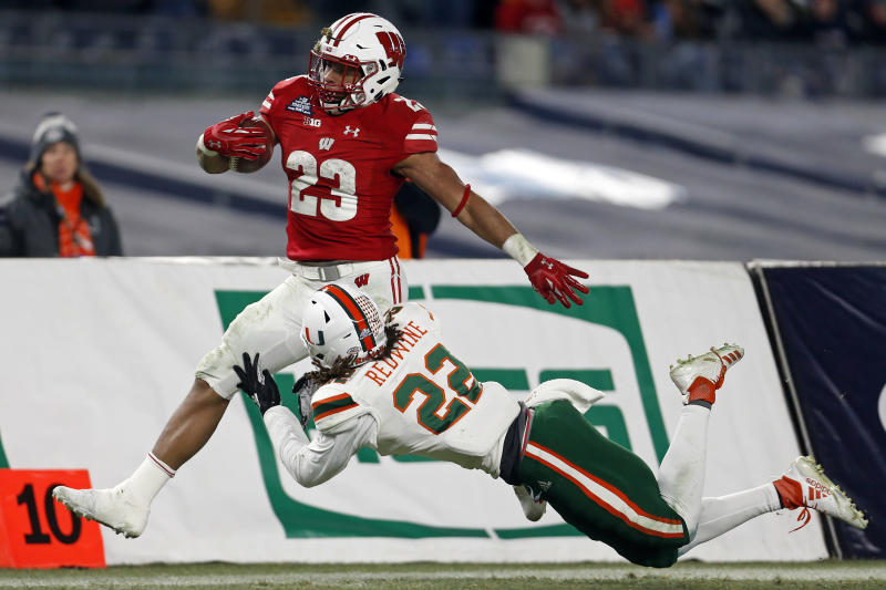 Wisconsin running back Jonathan Taylor (23) is tackled by Miami defensive back Sheldrick Redwine (22) during the second half of the Pinstripe Bowl NCAA college football game Thursday, Dec. 27, 2018, in New York. Wisconsin defeated Miami 35-3. (AP Photo/Adam Hunger)