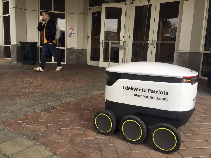 A Starship robot stands by at George Mason University campus in Fairfax, Va., Wednesday, Jan. 23, 2019.   A fleet of high-tech robots is now deployed at the northern Virginia university to serve the noble purpose of delivering pizza, doughnuts and coffee on demand to students who summon them. (AP Photo/Matthew Barakat)