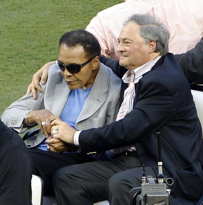 Muhammad Ali, left, rides onto the field with Miami Marlins owner Jeffrey Loria during Opening Day events before a baseball game between the Miami Marlins and the St. Louis Cardinals, Wednesday, April 4, 2012, in Miami. (AP Photo/Wilfredo Lee)