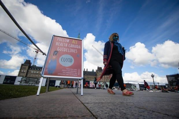 A person in a mask walks past a sign on Parliament Hill urging people to follow Health Canada's COVID-19 guidelines. (Trevor Pritchard/CBC - image credit)