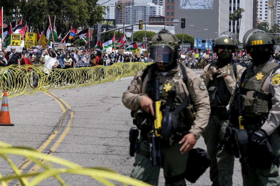 Police officers keep watch outside the Federal Building as demonstrators march to Israeli Consulate during a protest against Israel and in support of Palestinians, Saturday, May 15, 2021 in the Westwood section of Los Angeles. (AP Photo/Ringo H.W. Chiu)