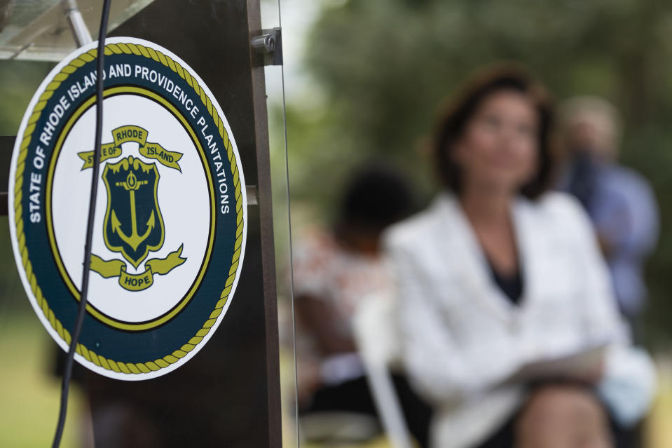"""FILE - In this Monday, June 22, 2020, file photo, the seal of the State of Rhode Island decorates a podium as Gov. Gina Raimondo looks on at right during a news conference where she announced that she has signed an executive order to remove the phrase """"Providence Plantations"""" in the state's formal name from some official documents and executive agency websites in Providence, R.I. Rhode Island changed its official name to remove the word """"plantations."""" (AP Photo/David Goldman, File)"""