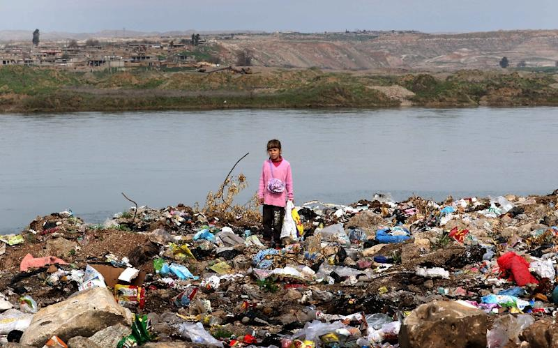 An Iraqi girl stands amid garbage on the banks of the Tigris River in the village of Wana, some 10 kms south of the Mosul Dam (AFP Photo/Safin Hamed)