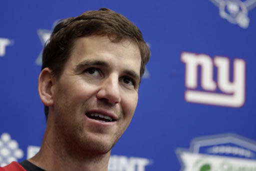 FILE - In an April 25, 2018 file photo, New York Giants quarterback Eli Manning speaks to reporters during NFL football training camp, in East Rutherford, N.J. If you want to get an insight into what makes Eli Manning tick, watch the two-time Super Bowl MVP work with kids at a summer football camp. Talking about football to three or four dozen attentive young players is something the New York Giants quarterback enjoys, whether the topic is hydration, catching passes, doing things in practice so they become second nature in games, focusing or simply just getting better. (AP Photo/Julio Cortez, File)